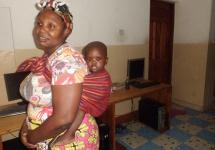 Bahati auf dem Rücken von Constance, die für die Kinder im MRC den Haushalt führt.